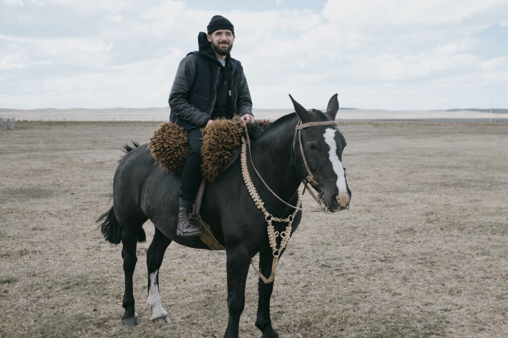 Embassy co-founder on a horse in Patagonia, scouting sheep farms for an ethical label that was sourcing from Argentina – not exactly feeling at home - Embassy of Bricks and Logs, Why we don't use Wool